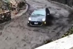 Car Speeds Down Road Trying To Escape Fast Moving River of Mud 10