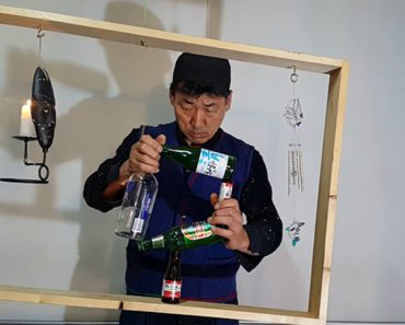 Balancing Expert Stacks Bottles To Form The Shape Of A Square Inside Of A Wobbly Wooden Frame 1
